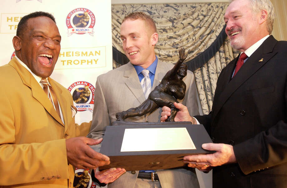 Heisman Trophy winner Jason White, center, a quarterback from Oklahoma, holds the Heisman Trophy with former Oklahoma Heisman Trophy winners Billy Sims (1978), left, and Steve Owens (1969) at the Yale Club in New York Saturday, Dec. 13, 2003. White is  a native of Tuttle, Okla., population 6,019 as of the 2010 Census and Sims is a native of Hooks, population 2,973 in 2010. Photo: KATHY WILLENS, AP / AP