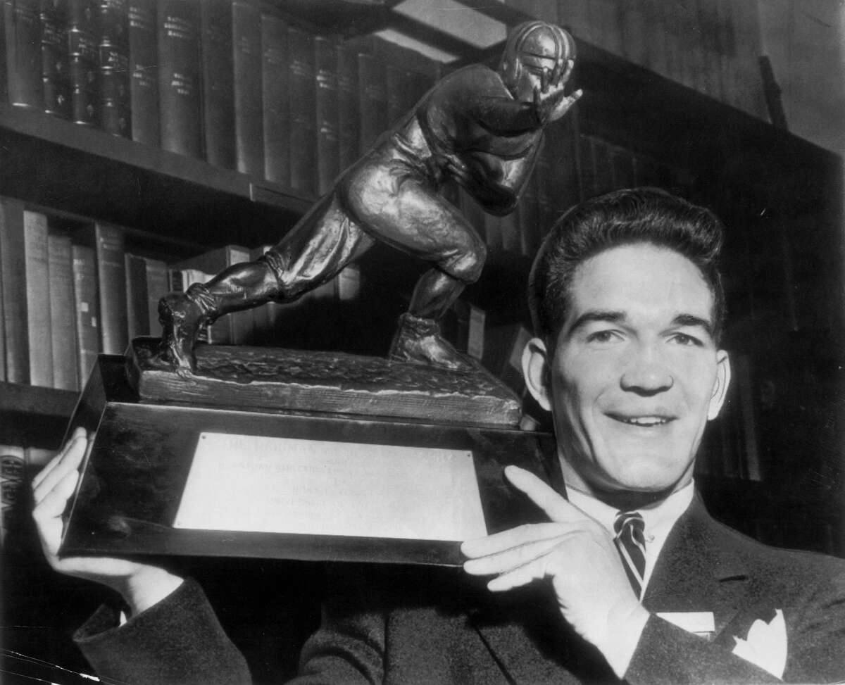 Oklahoma halfback Billy Vessels holds his 1952 Heisman Trophy in a file photo, date and location not known. Vessels was a native of Cleveland, Okla., population 3,282 as of the 2010 Census.