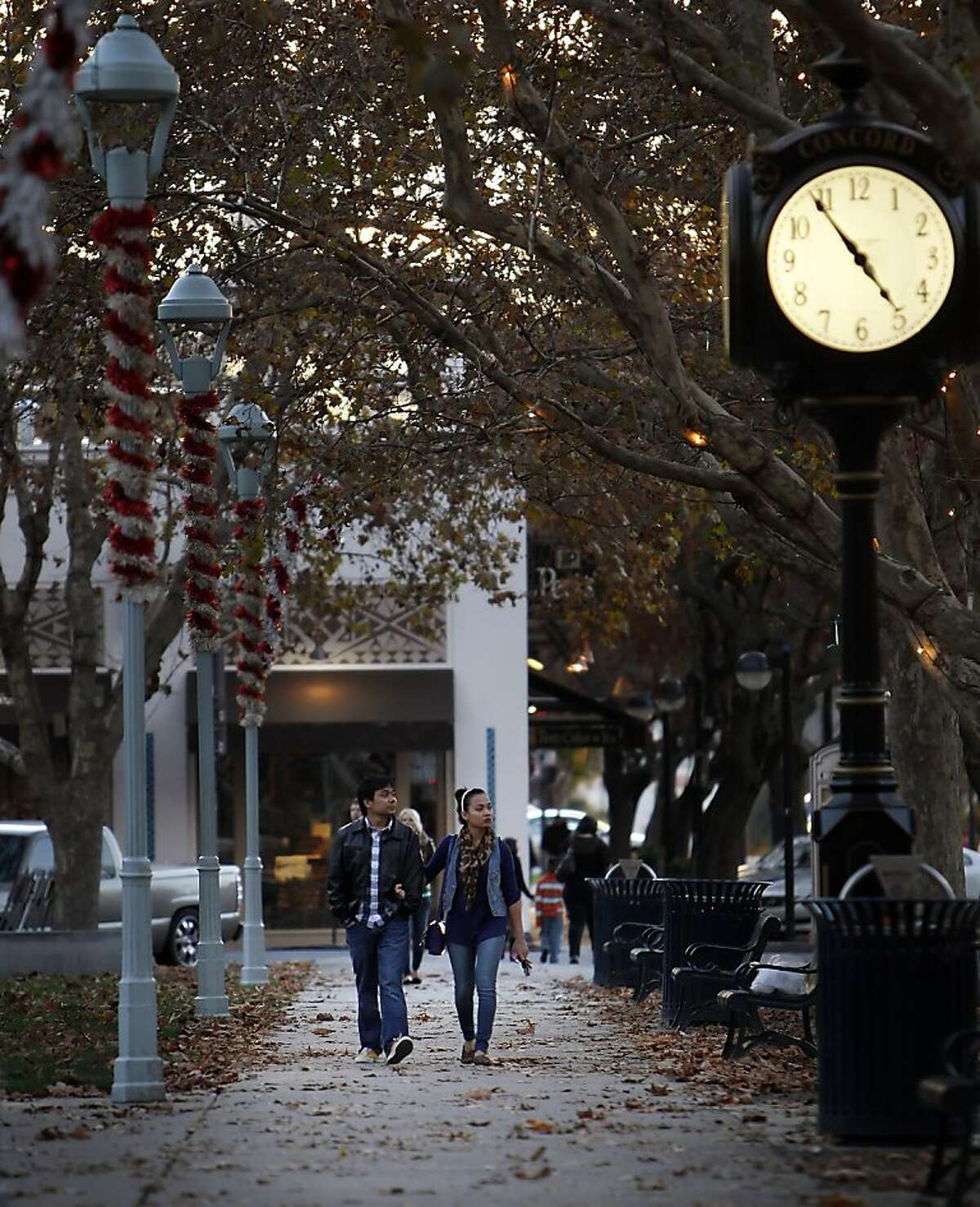 A couple walks along Salvio Street at Todos Santos Plaza in Concord, Calif., on Thursday, November 22, 2012. Todos Santos Plaza in Concord, Calif., was dedicated by Concord pioneer, Don Salvio Pacheco, in 1868 as the town square of the little 20-block town of Todos Santos, which was shortly renamed Concord. This 2.5 acre plot is filled with flowers, trees, benches and picnic tables. Today, Todos Santos Plaza is still the town's center and home to concerts, a fall festival, a Fourth of July parade and many other community events.