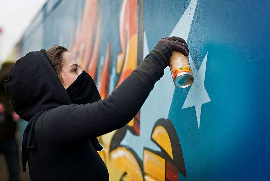 "German artist MadC, a.k.a. Claudia Walde, works on a mural with a spray can. Left, one of her smaller works from the ""Over the Edge"" solo exhibition, showing through Jan. 5 at the First Amendment Gallery in San Francisco. Photo: Marco Prosch"
