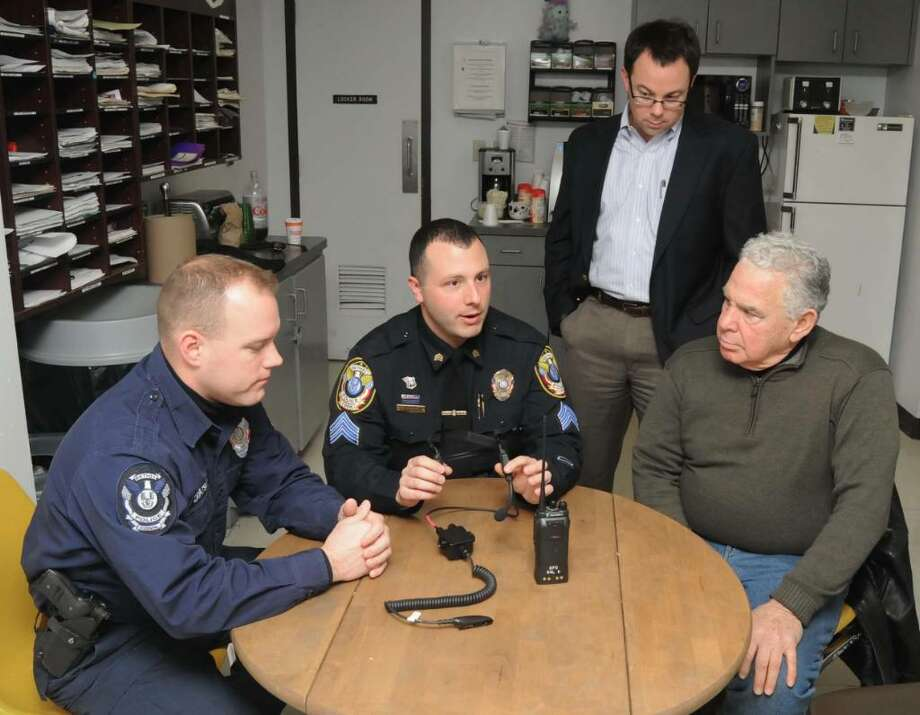 Bethel, CT police officers, left to right, Mathew Zavatsky and Sargent Michael Libertini, demonstrate new radio headphones, at Bethel Police Headquarters, donated to the Bethel Emergency Unit, by Richard Verti, right, of Bethel, CT, and his son, Curtis Verdi, 2nd from right, on Friday, Dec. 18, 2009. Photo: Jay Weir / The News-Times