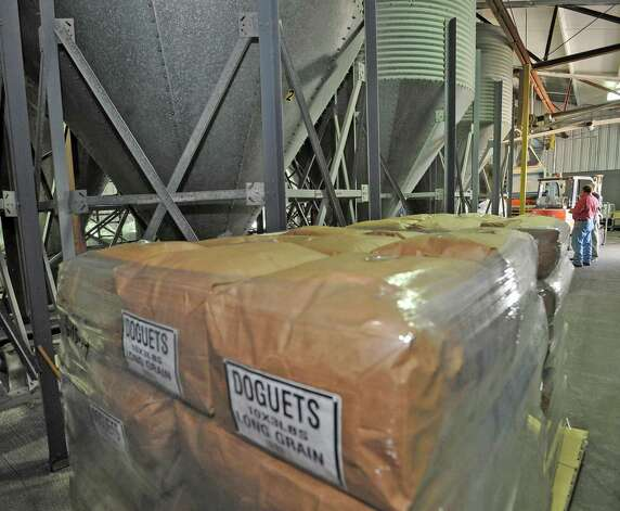 Bags of long grain rice sit on a pallet as Mike Doguet, far right,  discusses the pros and cons of the new farm bill being debated in Congress on Friday June 15, 2012, and how likely  it will not benefit rice farmers, because in the past it hasn't.  He was walking through his mill on College street and had stopped to watch some of the newly bagged white rice drop off a conveyer belt. Corn, soybeans and wheat growers usualyl fare much better.   Dave Ryan/The Enterprise Photo: Dave Ryan