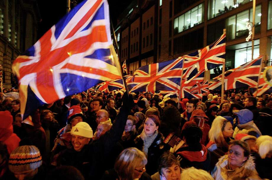 Loyalist protestors, some of them carrying British flags, gather as councillors debate whether or not to keep the flag flying at City Hall, outside City Hall, Belfast, Northern Ireland, Monday, Dec. 3, 2012. A Protestant mob stormed into the grounds of Belfast City Hall and clashed with police after the council's Catholic majority voted to remove the British flag from the building for most of the year. Authorities say two police officers and a security guard were wounded during Monday night's melee in the parking lot of the city hall. (AP Photo/PA, Paul Faith) UNITED KINGDOM OUT, NO SALES, NO ARCHIVE Photo: Paul Faith, Associated Press / PA