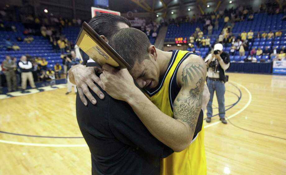 Quinnipiac's senior James Feldine, left, hugs  head coach Tom Moore after the Northeast Conference championship NCAA basketball game against Robert Morris in Hamden, Conn., Wednesday, March 10, 2010. Robert Morris won the game 52-50. (AP Photo/Thomas Cain) Photo: Thomas Cain, AP / FR170131 AP