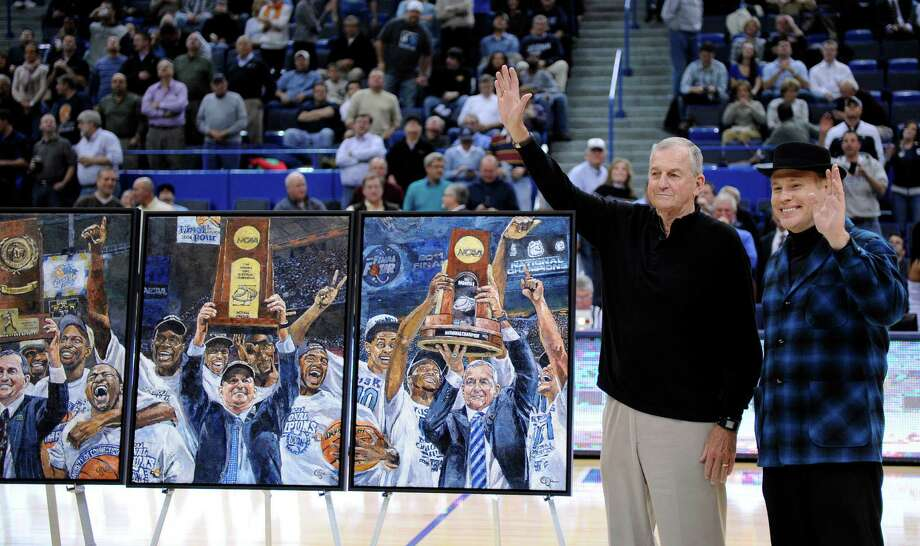 Former Connecticut coach Jim Calhoun, left, and artist Opie Otterstad wave to the crowd during a halftime ceremony of an NCAA college basketball game between Connecticut and New Hampshire, Thursday, Nov. 29, 2012, in Hartford, Conn. Otterstad's paintings commemorate Connecticut's three national championships. (AP Photo/Fred Beckham) Photo: Fred Beckham, Associated Press / FR153656 AP