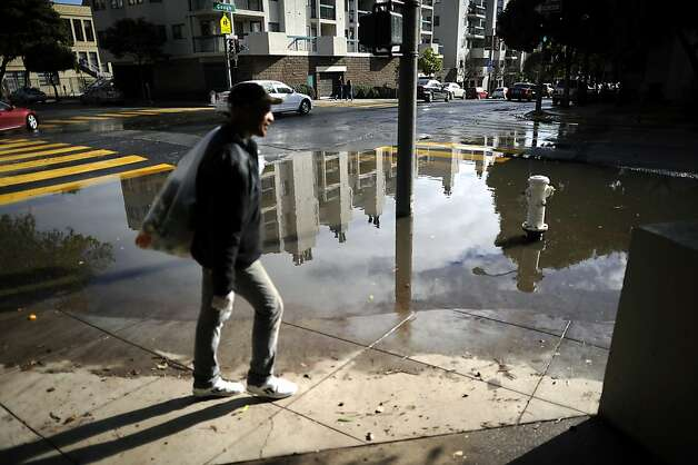 a man walks around a large puddle of standing water on the corner of Gough and Golden Gate in San Francisco.  A series of storms passed through the Bay Area on Sunday December 2nd, 2012, dumping rain accompanied by high winds. Photo: Michael Short, Special To The Chronicle