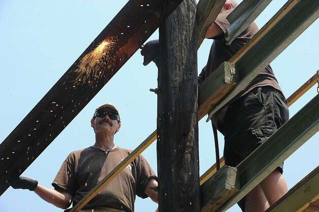 A work crew repairs the storm-damaged billboard in Rose City that once criticized Vidor police for botching the investigation into the 1991 murder of Kathy Page. Page's father James Fulton said a new sign will be installed, but would not comment on its message. Fulton did say that the message would not be nice. Photo taken Monday, May 21, 2012 Guiseppe Barranco/The Enterprise Photo: Guiseppe Barranco, STAFF PHOTOGRAPHER / The Beaumont Enterprise