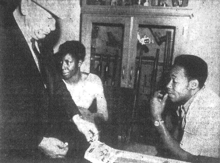 Sherriff Bill Hauck inspects narcotics and narcotics paraphernalia confiscated from the home of Mr. and Mrs. Theotis Harris (seated), in the 200 block of Ferguson on the East Side. It was the first narcotics charge filed against East Side residents in about four years, and Hauck's investigation was the first sheriff's probe within the limits of San Antonio for as many years as many courthouse officials can remember. Published in the San Antonio Express Dec. 6, 1962. Photo: File Photo