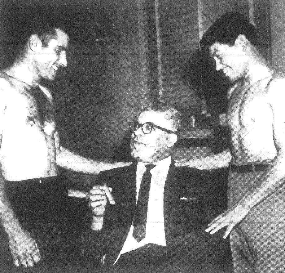 Why shouldn't Vic Graffio, left, and Jose Luis Cruz have happy smiles and kind words for the middle man, promoter Reuben Rodriguez? He holds the purse strings. Boxers Graffio and Cruz will put on expressions much grimmer Tuesday night for their fight in Municipal Auditorium. Published in the San Antonio Express Dec. 4, 1962. Photo: File Photo