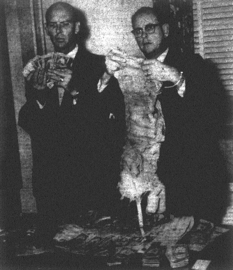 The ragged corset which held $16,020 in small bills collected by Mrs. Bessie Baker is gingerly handled by David Tomlinson, Bexar County Hospital District auditor, while J.P. Timmons, hospital assistant administrator, displays a fistful of the frayed money. Baker, believed to be more than 75, was thought financially unable to pay medical bills until officials found the moldy corset stuffed with cash. The woman, who was living on cat food and pecans, was removed by court order to the county home for the aged. Published in the San Antonio Express Dec. 15, 1962. Photo: File Photo