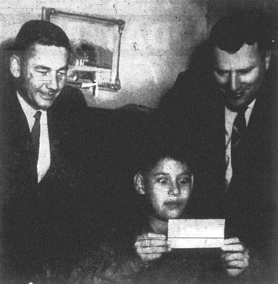 Manuel Briones' eyes pop as he looks at a $1,650 check given to the Mexican Baptist Children's Home by the Alamo Kiwanis Club. Looking on are Ford Sasser, Alamo Kiwanis committee chairman, left, and the Rev. J. Ivey Miller, superintendent of the home. The money will be used to buy feed grinder for cattle and pigs raised at the home as part of food supply for 146 children. Published in the San Antonio News Dec. 10, 1962. Photo: File Photo