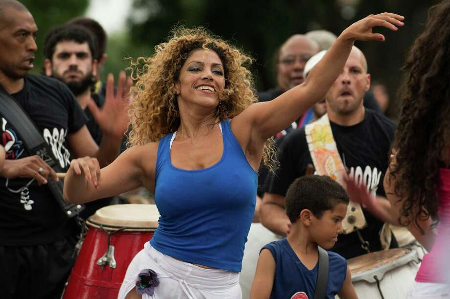 A dancer and drummers perform in front of the Afro-Uruguayan Culture House to celebrate the National Day of Candombe, Afro-Uruguayan Culture and Racial Equity, on December 3, 2012. Candombe music and dance was developed by African slaves during the colonial times in Montevideo and was recognized by UNESCO as a World Cultural Heritage of humanity. Photo: PABLO PORCIUNCULA, AFP/Getty Images / Pablo Porciuncula