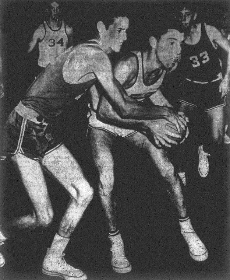Central Catholic's Tom Shaw, in dark uniform, and Bob Lawless of Baytown tussle for possession of the ball. No. 34 is Baytown's Robert Oliver and the Central player approaching from right is Lou Barber. Baytown won the game in the South San Antonio tournament, 54-36. Published in the San Antonio Express Dec. 8, 1962. Photo: File Photo