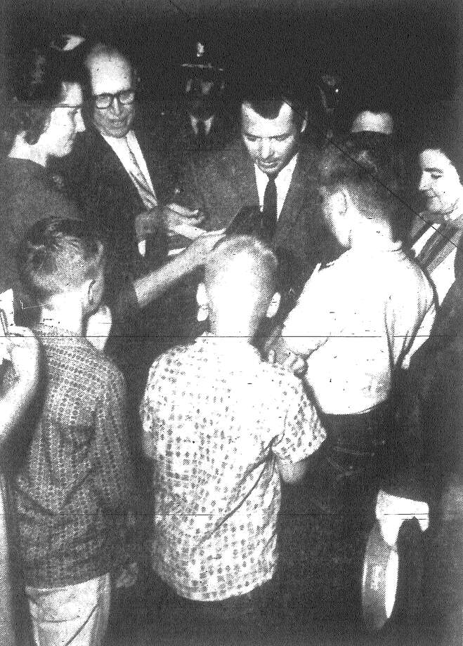 "Kids crowd about Audie Murphy, the most decorated soldier of World War II, at International Airport Wednesday, as he stages an impromptu autograph session. Murphy is in the Alamo City for the first showing of ""The Longest Day."" Published in the San Antonio News Dec. 20, 1962. Photo: File Photo"