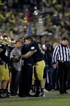 Notre Dame linebacker Manti Te'o hugs head coach Brian Kelly after he left his final home game late in the fourth of an NCAA college football against Wake Forest game in South Bend, Ind., Saturday, Nov. 17, 2012. Notre Dame defeated Wake Forest 38-0. (AP Photo/Michael Conroy) Photo: Michael Conroy, Associated Press / AP