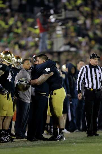 Notre Dame linebacker Manti Te'o hugs head coach Brian Kelly after he left his final home game late