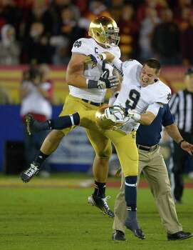 Notre Dame linebacker Manti Te'o, left, celebrates with Notre Dame wide receiver Robby Toma in the closing second of their their NCAA college football game against Southern California, Saturday, Nov. 24, 2012, in Los Angeles. (AP Photo/Mark J. Terrill) Photo: Mark J. Terrill, Associated Press / AP