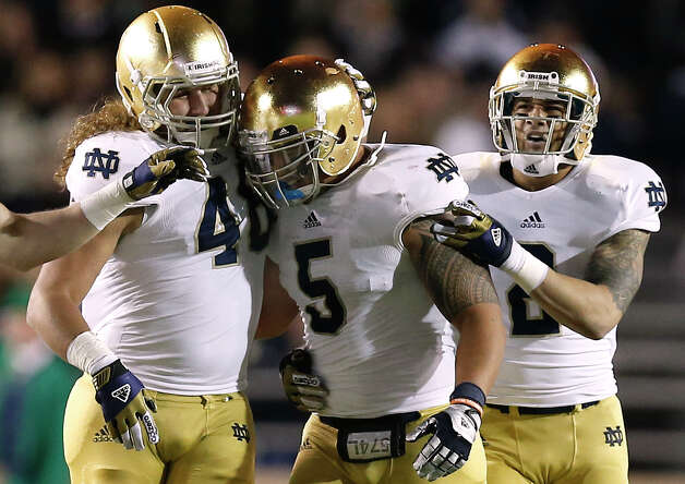 Notre Dame linebacker Manti Te'o is congratulated by teammates Dan Fox and Bennett Jackson, right, after his interception during the second half of Notre Dame's 21-6 win over Boston College in a NCAA college football game in Boston Saturday, Nov. 10, 2012. (AP Photo/Winslow Townson) Photo: Winslow Townson, Associated Press / FR170221 AP