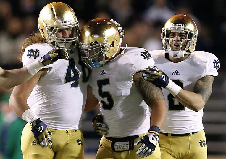 Notre Dame linebacker Manti Te'o is congratulated by teammates Dan Fox and Bennett Jackson, right, a