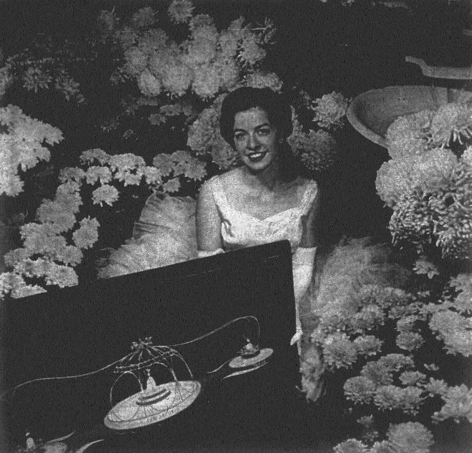 Rosalin Walker, one of the maids of honor to Miss Fiesta 1962, poses with a model of the float being built in Pasadena, Calif., to represent the Fiesta San Jacinto Association in the Tournament of Roses Parade there New Year's Day. She'll ride on the float with Miss Fiesta, Norma Martin, and the other maid of honor, Maxine Weynand. The float will be decorated with thousands of white and gold chrysanthemums. Published in the San Antonio News Dec. 27, 1962. Photo: File Photo