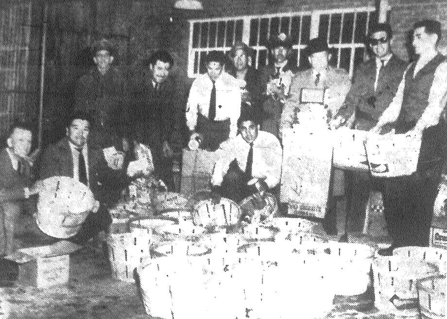 Mail carriers at Station A, 702 N. Medina, load up 100 baskets with groceries as Postmaster Dan Quill looks on. The carriers annually contribute the groceries and deliver them to 100 needy families on their routes. Published in the San Antonio Express Dec. 25, 1962. Photo: File Photo