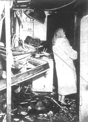 Mrs. John Cessna examines the damage to the garage apartment behind her home in the 2100 block of Magnolia following a Monday morning explosion. The occupant of the apartment, Ken Rozell, 34, escaped the blast with only singed hair and eyebrows. Published in the San Antonio Express Dec. 25, 1962. Photo: File Photo