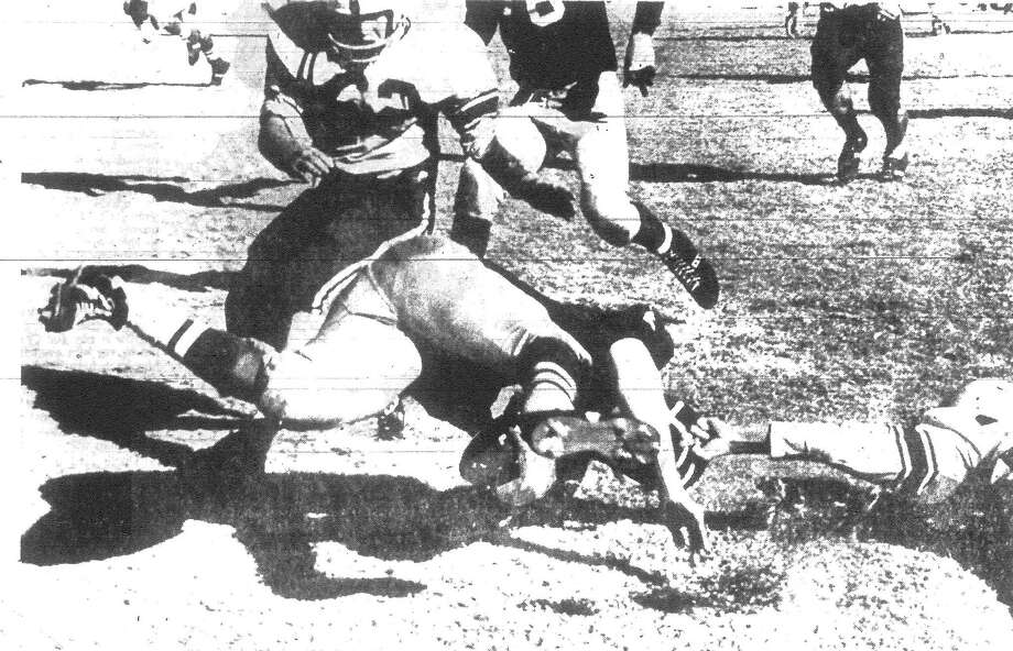 This illegal facemask tackle of Brackenridge halfback Pete Bautista by an unidentified Borger Bulldog was a big aid to the now state AAAA champions when they drove for the go-ahead touchdown at Abilene last Saturday. Bautista had been stopped with a five-yard gain on a pass from quarterback Victor Castillo, but the officials levied a 15-yard penalty for mask-tackling and the ball moved to the Borger 20. Five plays later Brackenridge scored to take the lead 14-8 and, though harried, was never headed as it won the championship 30-26. Published in the San Antonio Light Dec. 24, 1962. Photo: File Photo