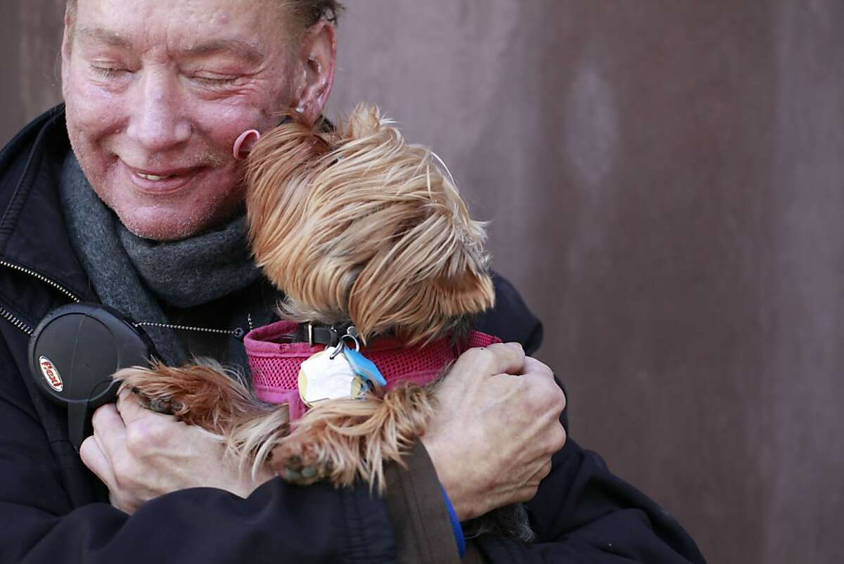 Robert Runkle hugs his dog Lola in front of his Potrero Hill apartment on Monday Dec. 03, 2012 in San Francisco, Calif. Two weeks Lola was stolen from Runkle's car while he was receiving dialysis treatment, and just when he has given up all hope of ever getting his companion back, she was returned after being found in Oakland.