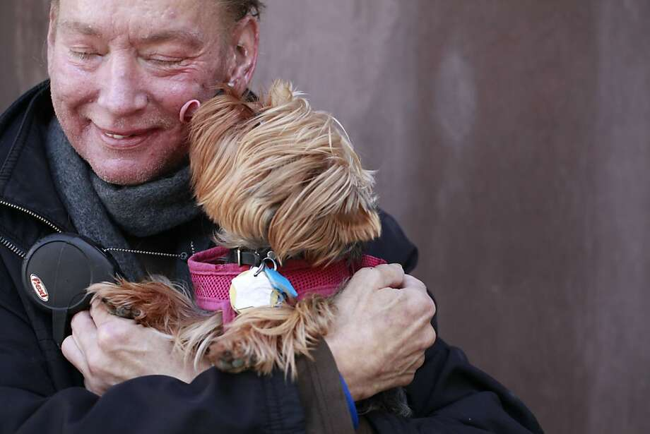 Robert Runkle hugs his dog, Lola, in front of his Potrero Hill apartment. Lola was stolen from his car two weeks ago. Photo: Mike Kepka, The Chronicle