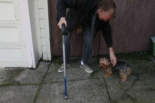Robert Runkle pets his dog Lola in front of his Potrero Hill apartment on Monday Dec. 03, 2012 in San Francisco, Calif. Two weeks Lola was stolen from Runkle's car while he was receiving dialysis treatment, and just when he has given up all hope of ever getting his companion back, she was returned after being found in Oakland. Photo: Mike Kepka, The Chronicle