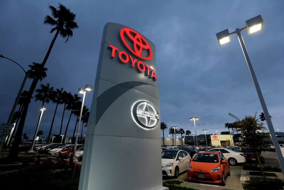 In this Thursday, Nov. 8, 2012, photo, a Toyota dealership signs glows over a car lot in Tustin Calif. A better economy and extra demand after Superstorm Sandy lifted U.S. auto sales in November. (AP Photo/Chris Carlson) Photo: Chris Carlson