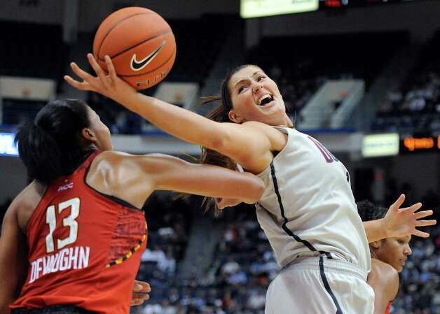 Connecticut's Stefanie Dolson, right, reaches back to grab a pass as Maryland's Alicia DeVaughn (13) defends during the second half of an NCAA college basketball game in Hartford, Conn., Monday, Dec. 3, 2012. Dolson was top scorer for Connecticut with 14 points in the team's 63-48 win over Maryland. (AP Photo/Jessica Hill) Photo: Jessica Hill, Associated Press / FR125654 AP