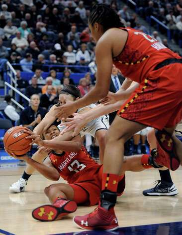 Maryland's Alicia DeVaughn (13) looks to pass to Tianna Hawkins, right, while pressured by Connecticut's Kelly Faris, center, during the first half of an NCAA college basketball game in Hartford, Conn., Monday, Dec. 3, 2012. (AP Photo/Jessica Hill) Photo: Jessica Hill, Associated Press / FR125654 AP