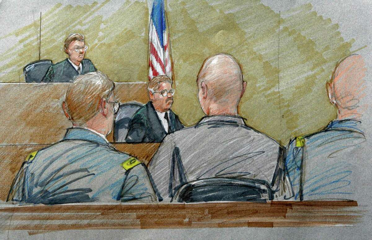 In a sketch, Maj. Nidal Hasan (center, back showing) sits with his defense team and before a courtroom reporter and Col. Gregory Gross (left rear) at a hearing in July 2011. Gross has been removed as judge in the case.