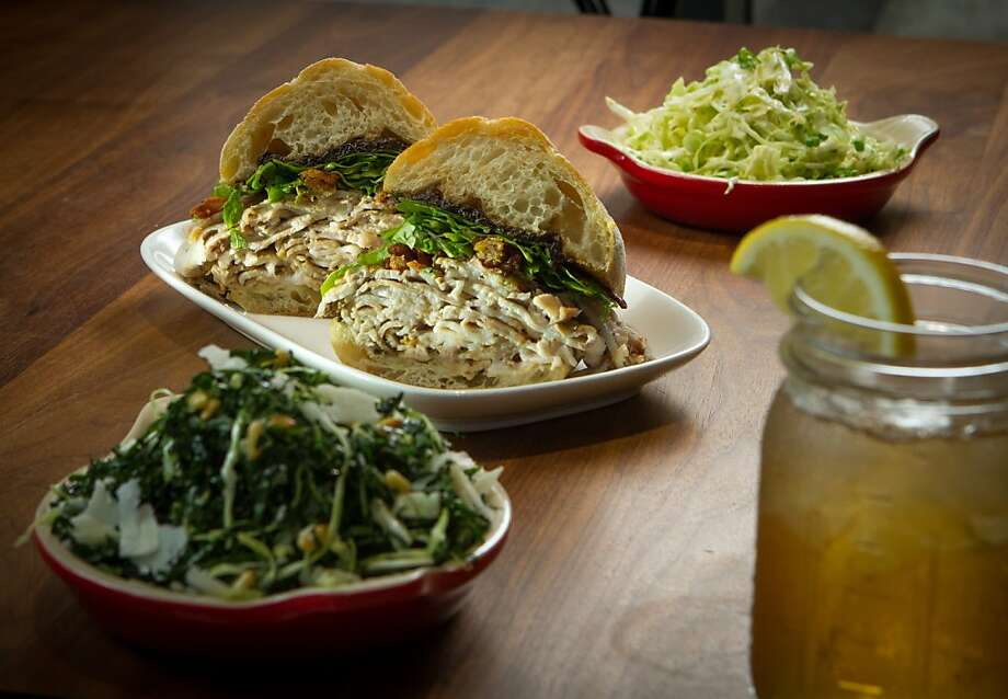 The rotisserie porchetta with sides of cole slaw (background), and kale salad at Split Bread, one of the newer eating places at the Metreon in San Francisco. Photo: John Storey, Special To The Chronicle