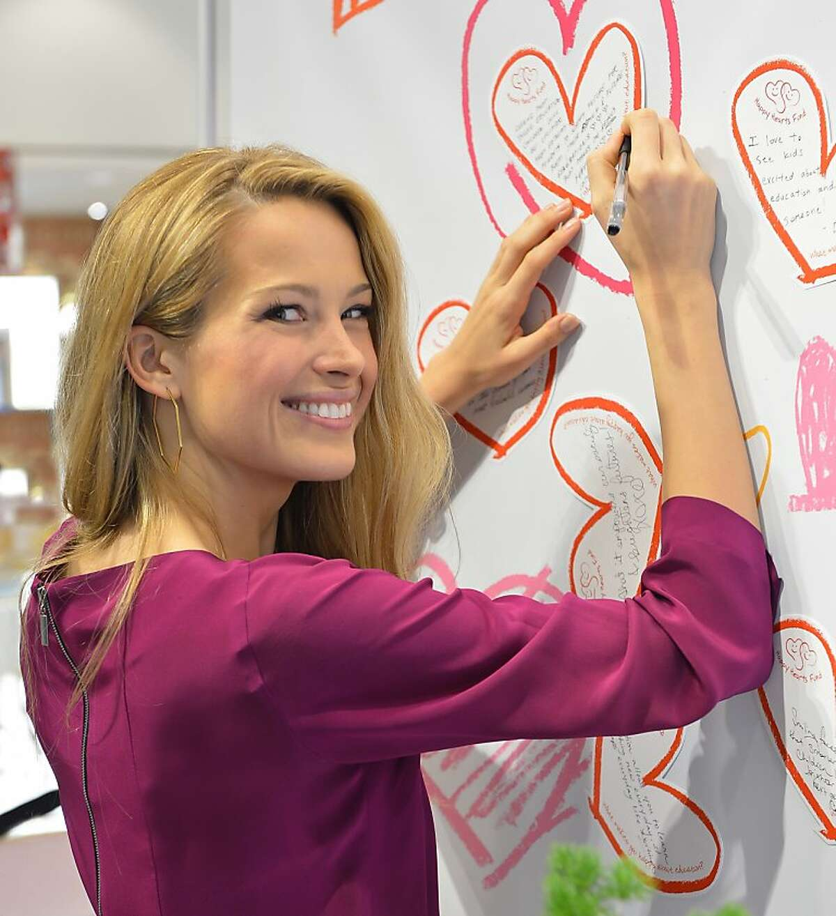 """Petra Nemcova signing bottle of Clinique's Happy Heart fragrance at the celebration of the new partnership with Clinique and her global charity, Happy Hearts Fund at Macy's Union Square on November 30, 2012 in San Francisco, CA. SAN FRANCISCO, CA - NOVEMBER 30: Petra Nemcova signs the Clinique """"Happy Heart"""" Wall at the celebration of her new partnership with Clinique and her glabal charity, Happy Hearts Fund at Macy's Union Square on November 30, 2012 in San Francisco, California. (Photo by Steve Jennings/Getty Images For Clinique)"""