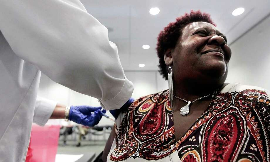 FILE - In a Tuesday, Oct. 30, 2012 file photo, Elizabeth Saint Victor winces as she gets a free flu shot from LPN Jean Buck courtesy of Baptist Healthcare in Memphis, Tenn., at the Central Library. Health officials say flu season is off to its earliest start in nearly 10 years _ and it could be a bad one. Officials said Monday, Dec. 3, 2012 that suspected flu cases have jumped in five southern states _ Alabama, Louisiana, Mississippi, Tennessee and Texas. An uptick in flu reports like this usually doesn't occur until after Christmas.  (AP Photo/The Commercial Appeal, Jim Weber, File) Photo: Jim Weber