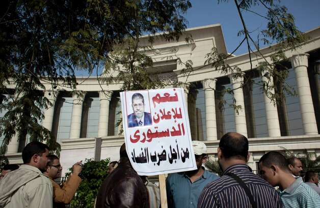 "A supporter of Egyptian President Mohammed Morsi holds a banner with his picture and Arabic that reads, ""yes for the constitutional declaration to stop corruption,"" during a protest in front of Egypt's top court, in Cairo, Egypt, Monday, Dec. 3, 2012. The Egyptian president's top legal adviser says the country's election commission has begun preparations for the referendum on Dec. 15 on a highly contentious draft constitution. (AP Photo/Nasser Nasser) Photo: Nasser Nasser"