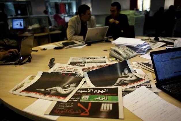"Egyptian journalists at the editorial room of al-Masri al-Youm daily newspaper next to copies of Egypt's most prominent newspapers running black background front pages with Arabic that reads, ""no to dictatorship, tomorrow free newspapers will obscure to protest the freedom's restrictions,"" and a picture of a man wrapped in newspapers with his feet cuffed, in Cairo, Egypt, Monday, Dec. 3, 2012. Eleven Egyptian newspapers are planning to suspend publication on Tuesday to protest against President Mohammed Morsi's decision to call a constitution referendum on 15 December. (AP Photo/Nasser Nasser) Photo: Nasser Nasser"