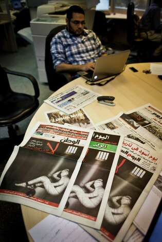 "An Egyptian journalist works at the editorial room of Al-Masry Al-Youm daily newspaper next to copies of Egypt's most prominent newspapers running black background front pages with Arabic that reads, ""no to dictatorship, tomorrow free newspapers will obscure to protest the freedom's restrictions,"" and a picture of a man wrapped in newspapers with his feet cuffed, in Cairo, Egypt, Monday, Dec. 3, 2012. Eleven Egyptian newspapers are planning to suspend publication on Tuesday to protest against President Mohammed Morsi's decision to call a constitution referendum on 15 December. (AP Photo/Nasser Nasser) Photo: Nasser Nasser"
