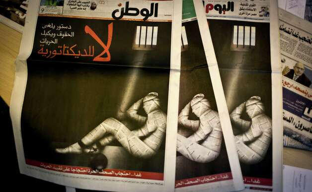 "Copies of Egypt's most prominent newspapers running black background front pages with Arabic that reads, ""no to dictatorship, tomorrow free newspapers will obscure to protest the freedom's restrictions"" and a picture of a man wrapped in newspaper with his feet cuffed, at the editorial room of Al Masry Al Youm daily newspaper in Cairo, Egypt, Monday, Dec. 3, 2012. Eleven Egyptian newspapers are planning to suspend publication on Tuesday to protest against President Mohammed Morsi's decision to call a constitution referendum on 15 December. (AP Photo/Nasser Nasser) Photo: Nasser Nasser"