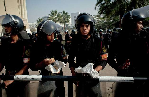 Riot policemen eat their lunch as they stand guard in front of Egypt's top court during a protest for supporters of Egyptian President Mohammed Morsi, unseen, in Cairo, Egypt, Monday, Dec. 3, 2012. The Egyptian president's top legal adviser says the country's election commission has begun preparations for the referendum on Dec. 15 on a highly contentious draft constitution. (AP Photo/Nasser Nasser) Photo: Nasser Nasser
