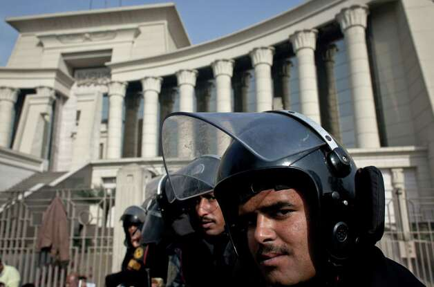 Riot policemen stand guard in front of Egypt's top court during a protest for supporters of Egyptian President Mohammed Morsi, unseen, in Cairo, Egypt, Monday, Dec. 3, 2012. The Egyptian president's top legal adviser says the country's election commission has begun preparations for the referendum on Dec. 15 on a highly contentious draft constitution. (AP Photo/Nasser Nasser) Photo: Nasser Nasser