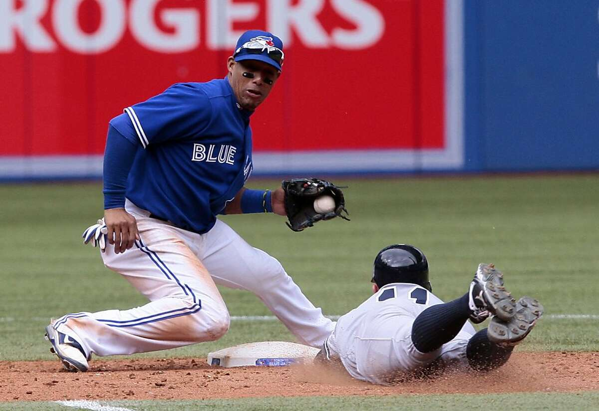 FILE - NOVEMBER 13: According to reports, the Miami Marlins will trade Jose Reyes, Josh Johnson, Mark Buehrle, John Buck and Emilio Bonifacio to the Toronto Blue Jays for Yunel Escobar, and prospects Jake Marisnick and Adeiny Hechevarria. TORONTO, CANADA - SEPTEMBER 29: Yunel Escobar #5 of the Toronto Blue Jays makes the play to catch Brett Gardner #11 of the New York Yankees stealing at second during MLB action at the Rogers Centre September 29, 2012 in Toronto, Ontario, Canada. (Photo by Abelimages/Getty Images)