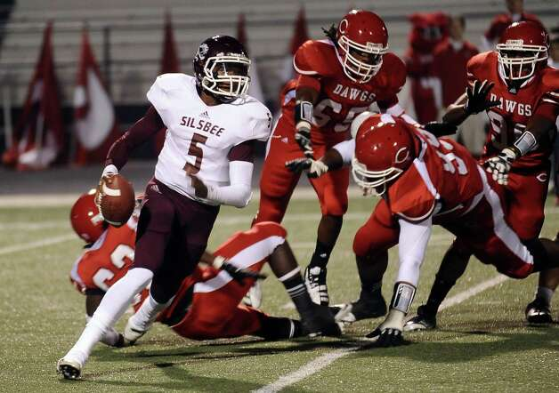 Silsbee quarterback Patrick Reed, 5, scrambles in the back field before making a great pass for another Silsbee first down during the Carthage High School Class 3A Division II state quarter finals game against Silsbee High School at the Abe Martin Stadium in Lufkin on November, 30, 2012. Photo taken: Randy Edwards/The Enterprise Photo: Randy Edwards