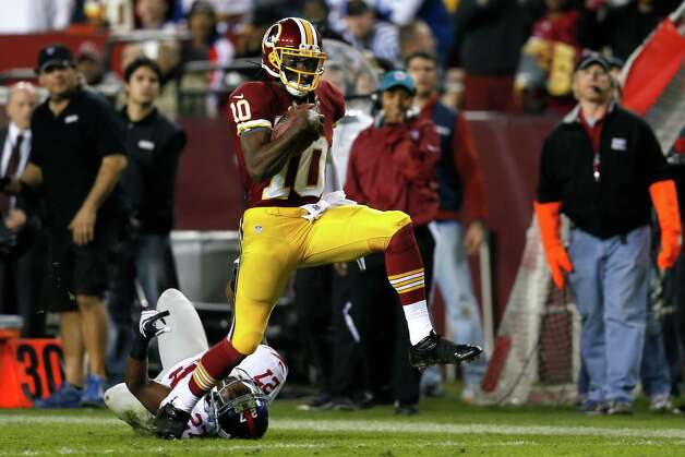 LANDOVER, MD - DECEMBER 03:  Quarterback Robert Griffin III #10 of the Washington Redskins runs for a 46-yard gain as he is taken down by  Stevie Brown #27 of the New York Giants in the second half at FedExField on December 3, 2012 in Landover, Maryland. Photo: Rob Carr, Getty Images / 2012 Getty Images