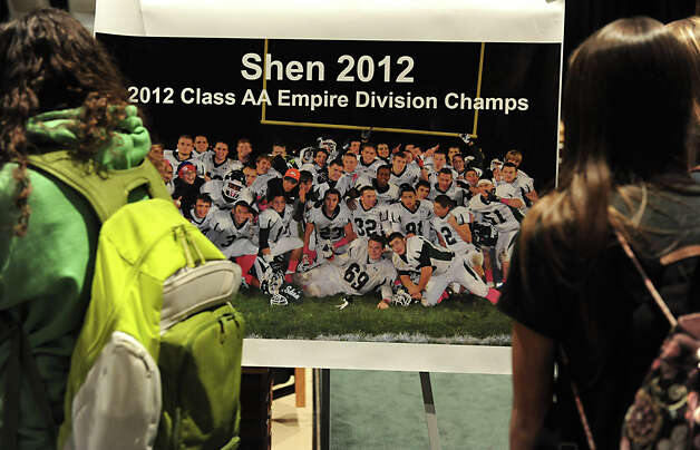 Students look at a football poster at a memorial set up in the auditorium at Shenendehowa High School Monday Dec. 3, 2012 in Clifton Park, N.Y. The memorial is set up for students to grieve together, to leave notes and flowers to honor the lives of Chris Stewart and Deanna Rivers, and to offer wishes for the emotional and physical recovery of Matt Hardy and Bailey Wind. Chris Stewart is #69 front and center in the poster.  (Lori Van Buren / Times Union) Photo: Lori Van Buren