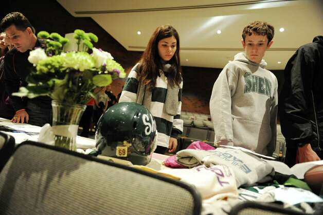 Students and faculty look at personal belongings of Chris Stewart at a memorial set up in the auditorium at Shenendehowa High School Monday Dec. 3, 2012 in Clifton Park, N.Y. The memorial is set up for students to grieve together, to leave notes and flowers to honor the lives of Chris Stewart and Deanna Rivers, and to offer wishes for the emotional and physical recovery of Matt Hardy and Bailey Wind. (Lori Van Buren / Times Union) Photo: Lori Van Buren