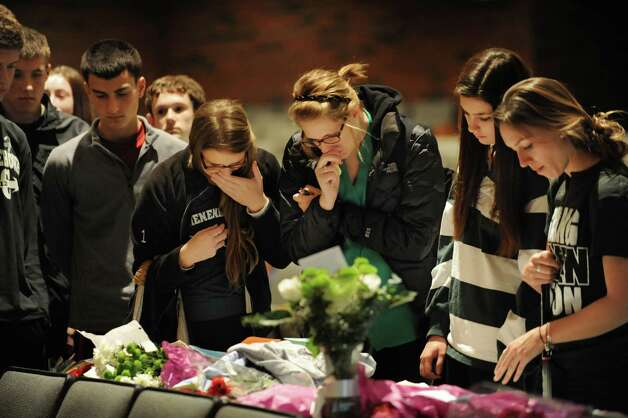 Students get emotional at a memorial set up in the auditorium at Shenendehowa High School Monday Dec. 3, 2012 in Clifton Park, N.Y. The memorial is set up for students to grieve together, to leave notes and flowers to honor the lives of Chris Stewart and Deanna Rivers, and to offer wishes for the emotional and physical recovery of Matt Hardy and Bailey Wind. Many students wrote the #69 for Chris and #19 for Deanna on their hands today. (Lori Van Buren / Times Union) Photo: Lori Van Buren