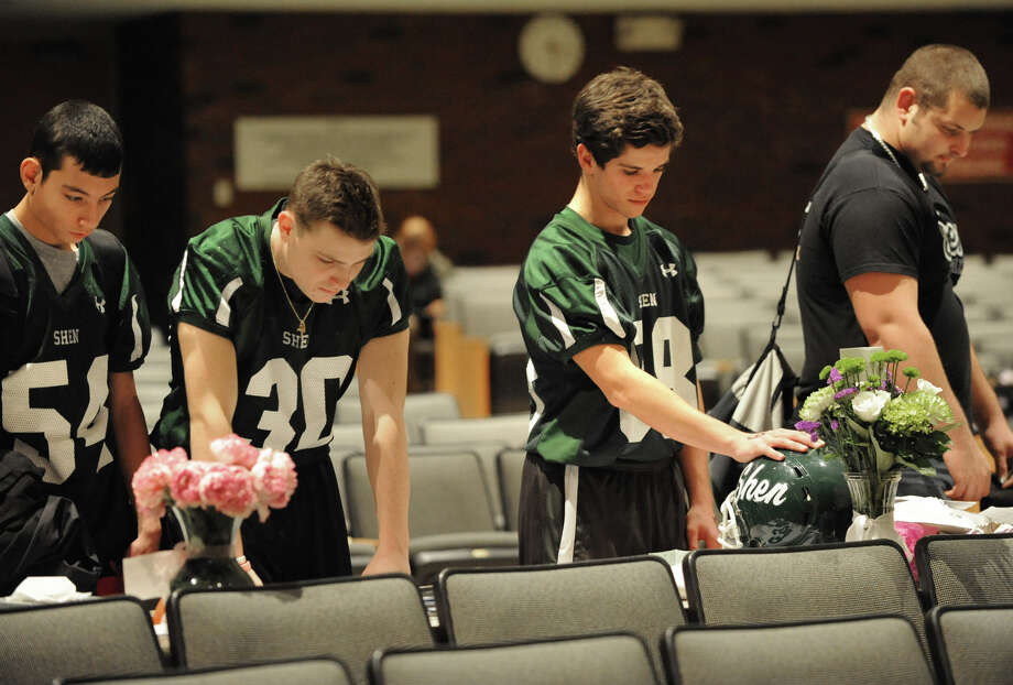 From let, football players Gary Roberts, Antonio Rossi, Matthew Hendrickson and Jacob Brooks walk through a memorial set up in the auditorium at Shenendehowa High School Monday Dec. 3, 2012 in Clifton Park, N.Y. The memorial is set up for students to grieve together, to leave notes and flowers to honor the lives of Chris Stewart and Deanna Rivers, and to offer wishes for the emotional and physical recovery of Matt Hardy and Bailey Wind. (Lori Van Buren / Times Union) Photo: Lori Van Buren